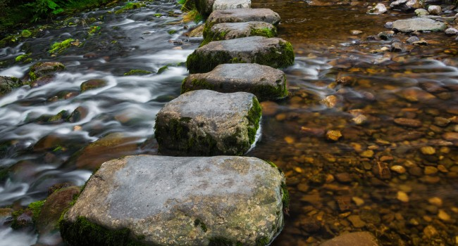 stepping-stones-over-river-and-small-waterfall